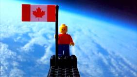 Lego man holding Canadian flag while in space